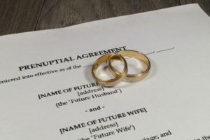 photo of prenuptial agreement documents with wedding rings