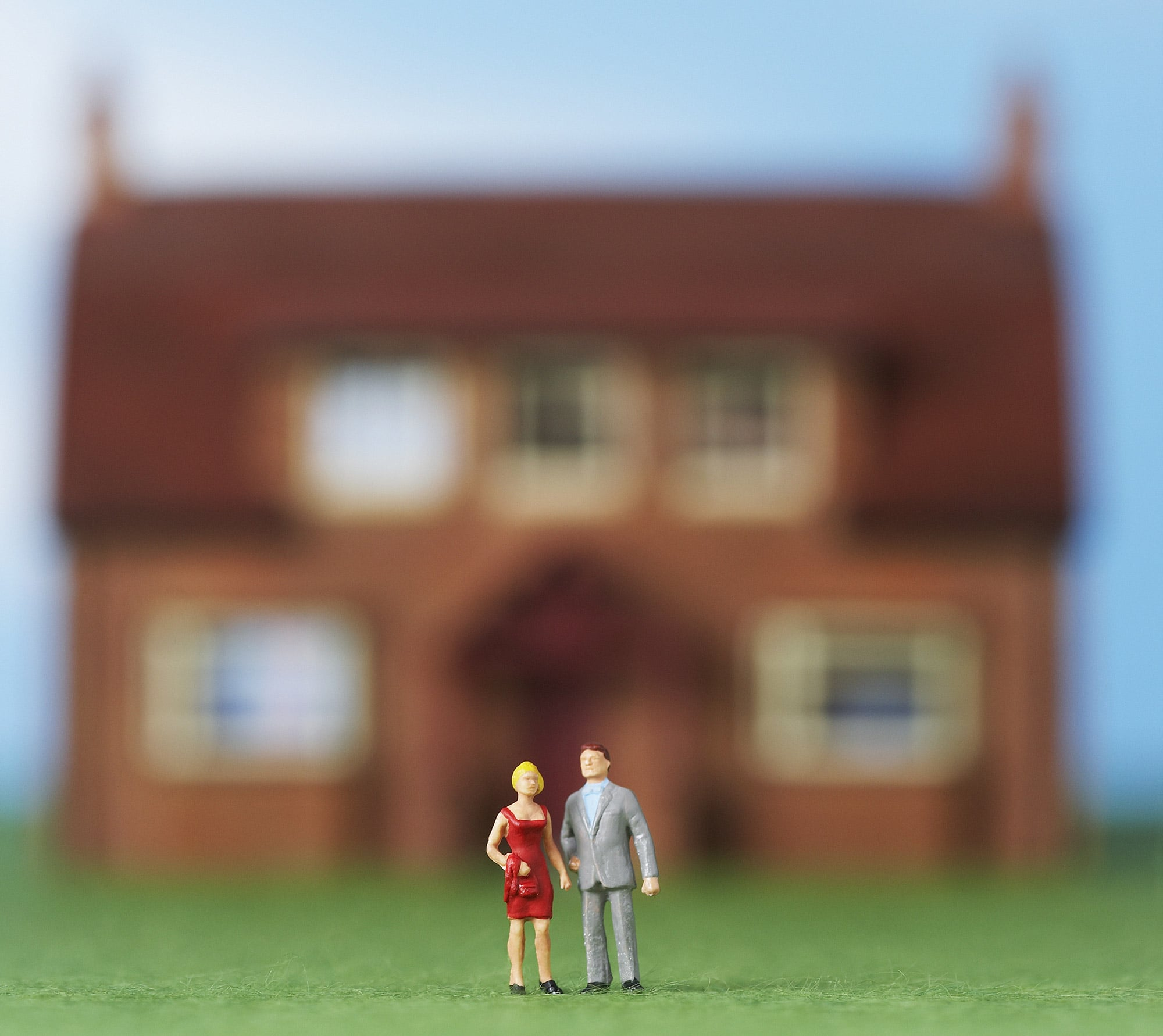photo of a miniature couple in front of a small house