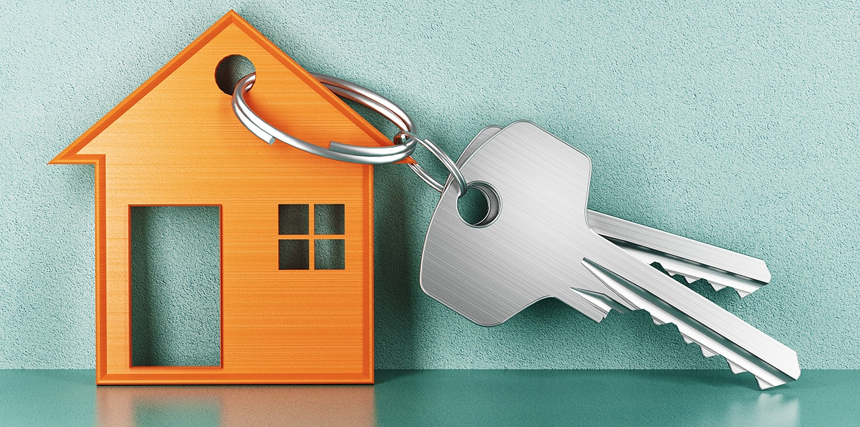 photo of a miniature house and set of keys